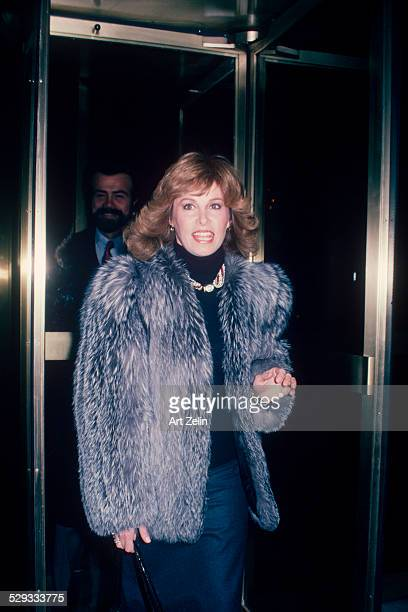 Stefanie Powers coming through a revolving door wearing a fur coat circa 1970 New York