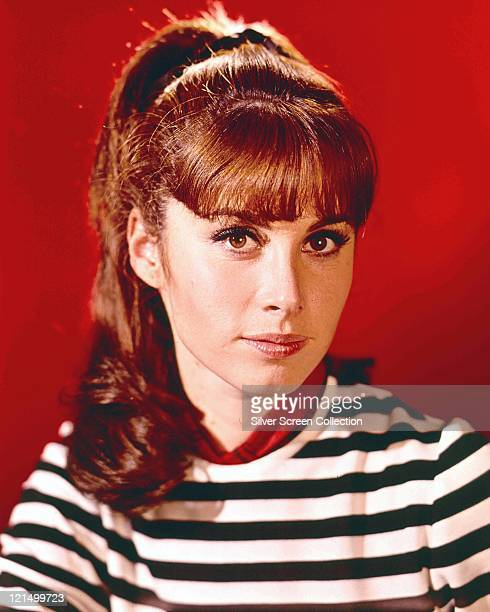 Stefanie Powers US actress wearing a blackandwhite striped top in a studio portrait against a red background issued as a publicity portrait for the...