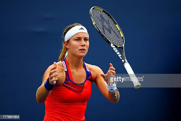 Stefanie Voegele of Switzerland catches her racquet after throwing it on the ground during her first round match against Anna Schmiedlova of Slovakia...