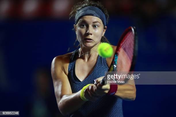 Stefanie Voegele of Switzerland returns a shot during a semifinal match between Stefanie Voegele of Switzerland and Rebecca Peterson of Sweden as...