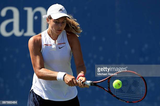 Stefanie Voegele of Switzerland returns a shot to Kurumi Nara of Japan during her first round Women's Singles match on Day Two of the 2016 US Open at...