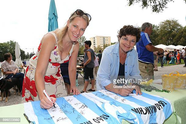 Stefanie von Poser and Monika Baumgartner sign Tshirts during the charity football game 'Kick for Kids' to benefit 'Die Seilschaft zusammen sind wir...