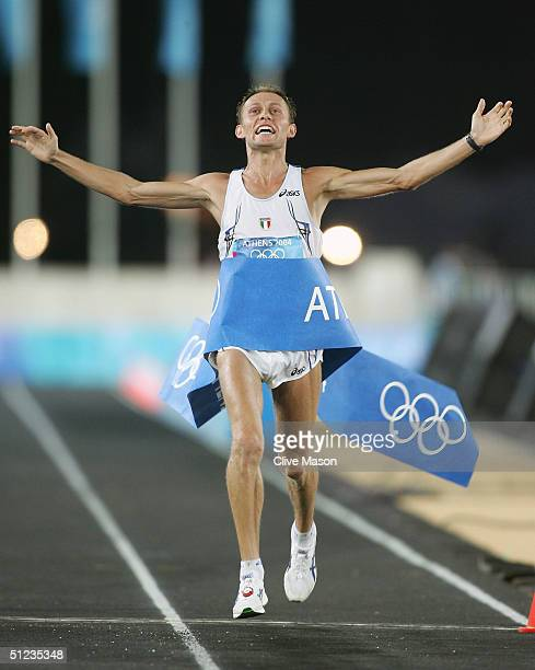 Stefano Baldini of Italy celebrates as he crosses the finish line first to win the gold medal in the men's marathon on August 29 2004 during the...