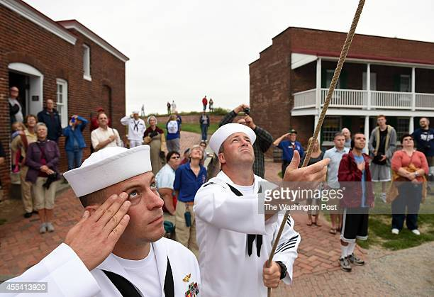 Stefano Casandra left of the United States Navy salutes a flag as it is lowered by ASC Sean Gregar center during the StarSpangled Spectacular which...