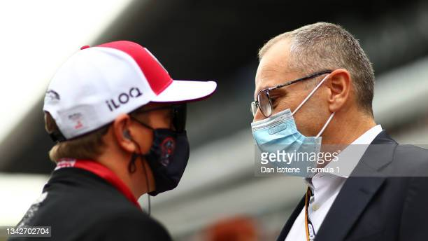 Stefano Domenicali, CEO of the Formula One Group, and Kimi Raikkonen of Finland and Alfa Romeo Racing talk on the grid before the F1 Grand Prix of...