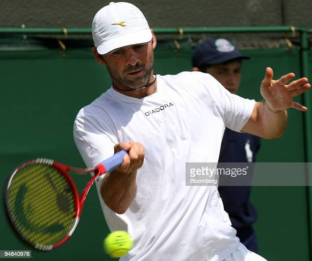 Stefano Galvani of Italy makes a return to Mikhail Youzhny of Russia unseen in their match at the Wimbledon tennis championships in southwest London...