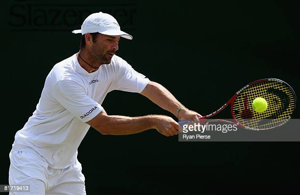 Stefano Galvani of Italy plays a backhand during the round two men's singles match against Mikhail Youzhny of Russia on day four of the Wimbledon...