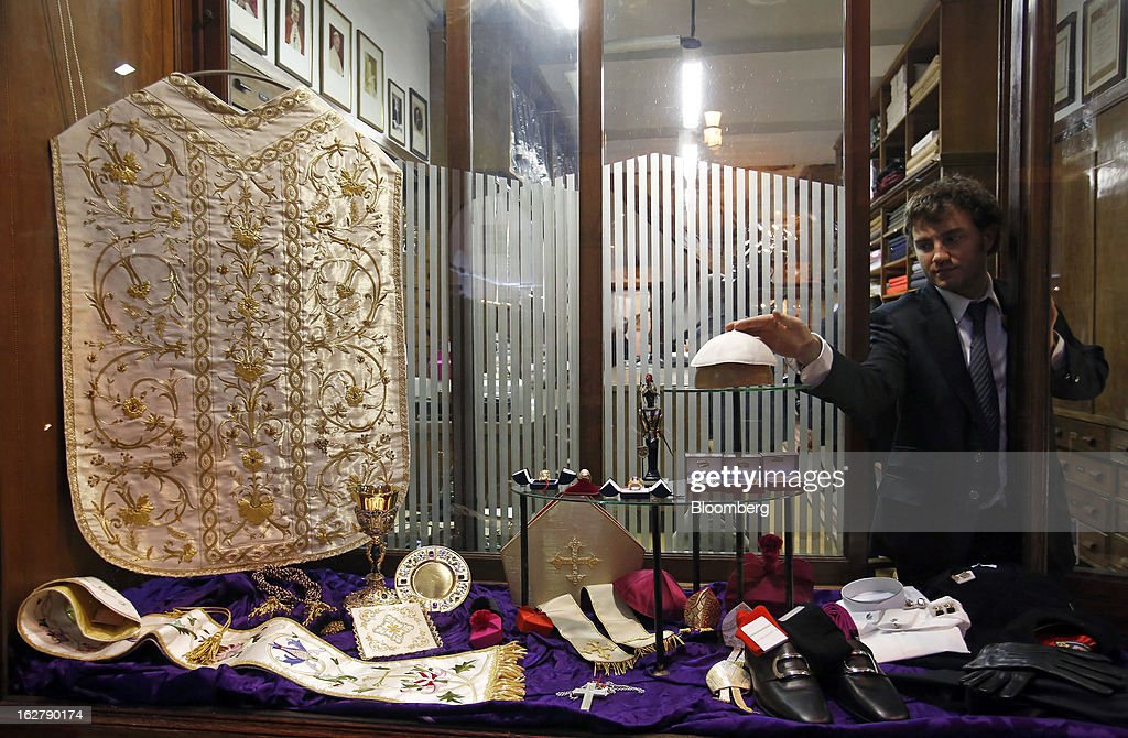 Stefano Gammarelli, an ecclesiastical tailor at Gammarelli, places a white papal skull cap in the window display of his family's store in Rome, Italy, on Friday, Feb. 22, 2013. Gammarelli was founded in 1797 under Pope Pius VI as tailors to the clergy, and lists other papal customers as John Paul I, Paul VI, and John XXIII. Photographer: Alessia Pierdomenico/Bloomberg via Getty Images
