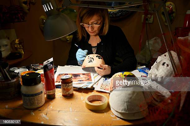 Stefano Gottardo's assistant, Manuela, paints a mask in the workshop during the carnival on February 2, 2013 in Venice. The 2013 edition of the...