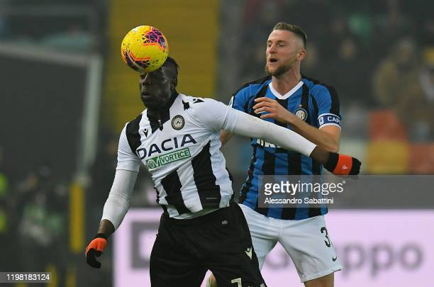 Stefano Okaka of Udinese Calcio competes for the ball with Milan Skriniar of FC Internazionale during the Serie A match between Udinese Calcio and FC...