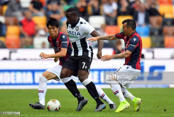 Stefano Okaka of Udinese Calcio competes for the ball with Takehiro Tomiyasu and Gary Medel of Bologna FC during the Serie A match between Udinese...