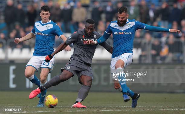 Stefano Okaka of Udinese Calcio is challenged by Jhon Chancellor and Dimitri Bisoli of Brescia Calcio during the Serie A match between Brescia Calcio...