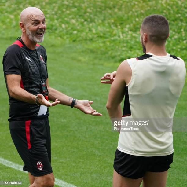 Stefano Pioli, Head Coach of AC Milan speaks with Ante Rebic during an AC Milan Training Session at Milanello on July 30, 2021 in Cairate, Italy.