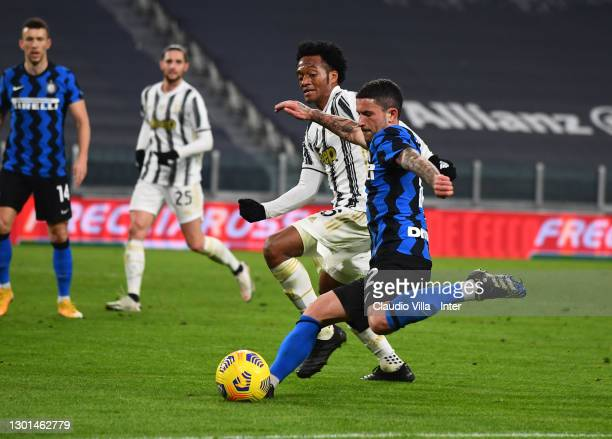 Stefano Sensi of FC Internazionale and Juan Cuadrado compete for the ball during the Coppa Italia semi-final Juventus and FC Internazionale at...