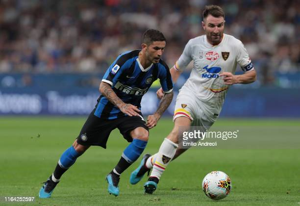 Stefano Sensi of FC Internazionale is challenged by Fabio Lucioni of US Lecce during the Serie A match between FC Internazionale and US Lecce at...