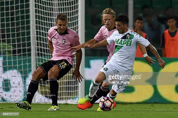 Stefano Sensi of Sassuolo holds off the challenge from Thiago Cionek and Oscar Hiljemark of Palermo during the Serie A match between US Citta di...