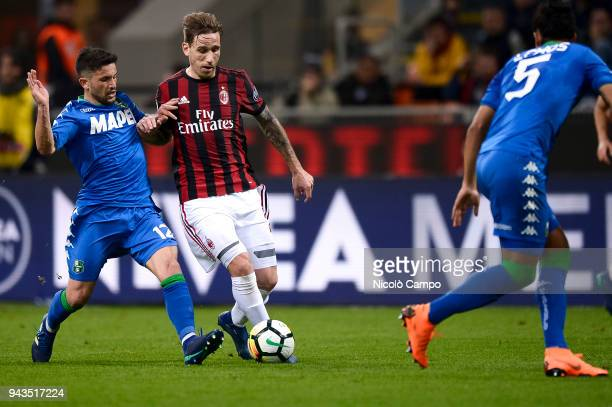 Stefano Sensi of US Sassuolo competes for the ball with Lucas Biglia of AC Milan during the Serie A football match between AC Milan ad US Sassuolo...