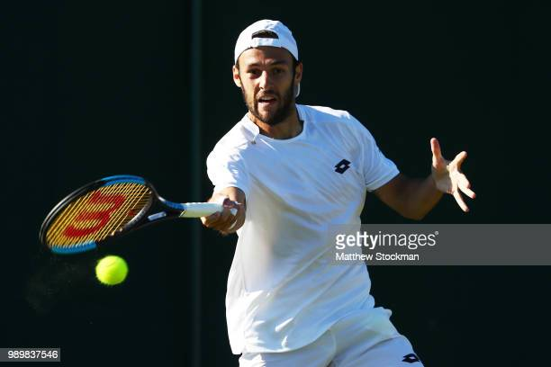 Stefano Travaglia of Italy returns against John Millman of Australia during their Men's Singles first round match on day one of the Wimbledon Lawn...