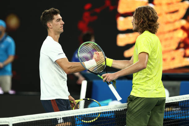 Stefanos Tsitsipas of Greece and Thanasi Kokkinakis of Australia embrace at the net following their Men's Singles second round match during day four...