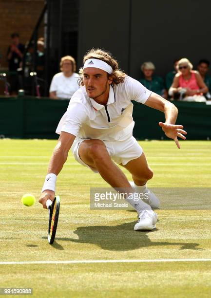 Stefanos Tsitsipas of Greece dives to play a backhand return against John Isner of the United States during their Men's Singles fourth round match on...