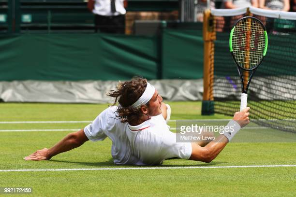Stefanos Tsitsipas of Greece falls to the court in an attempt to return a shot against Jared Donaldson of the United States during their Men's...