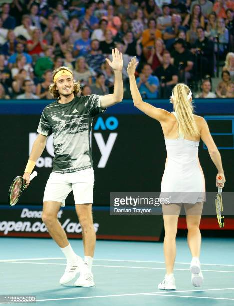 Stefanos Tsitsipas of Greece high fives Caroline Wozniacki of Denmark during the Rally for Relief Bushfire Appeal event at Rod Laver Arena on January...