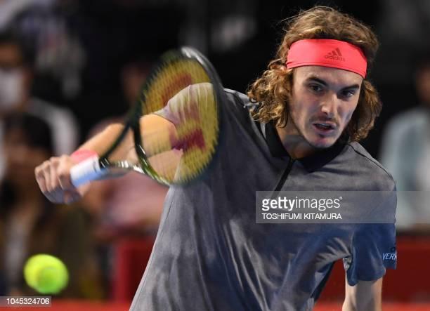 Stefanos Tsitsipas of Greece hits a return during his men's singles second round match against Australia's Alex de Minaur at the Japan Open tennis...