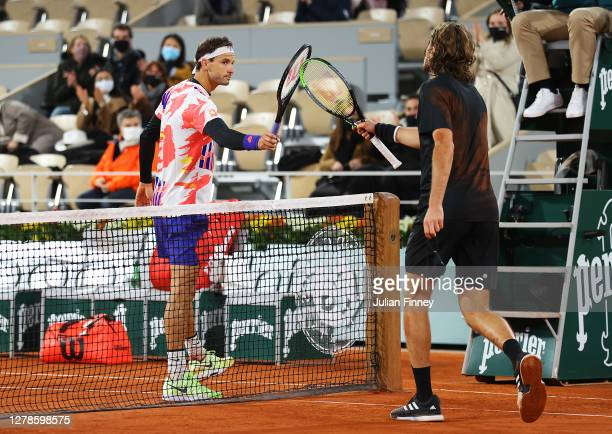 Stefanos Tsitsipas of Greece knocks racquets at the net with Grigor Dimitrov of Bulgaria following his victory in their Men's Singles fourth round...