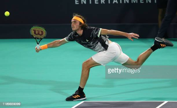 Stefanos Tsitsipas of Greece reaches to return the ball to Serbia's Novak Djokovic in their semifinal match of the Mubadala World Tennis Championship...