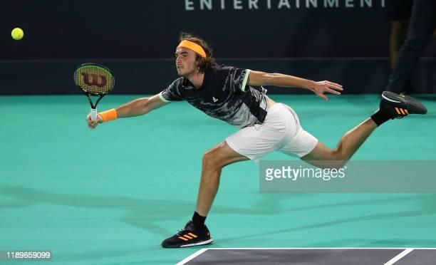 Stefanos Tsitsipas of Greece reaches to return the ball to Serbia's Novak Djokovic in their semi-final match of the Mubadala World Tennis...
