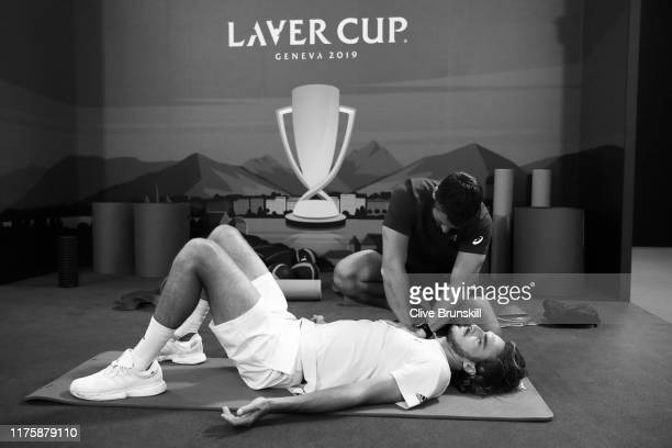 Stefanos Tsitsipas of Team Europe stretches with a trainer prior to a practice session ahead of the Laver Cup 2019 at Palexpo on September 19, 2019...