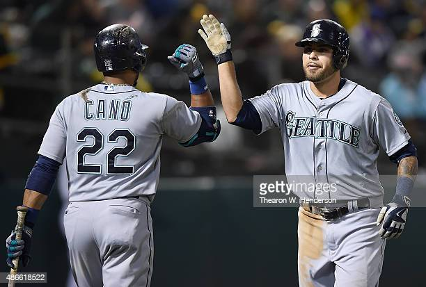 Stefen Romero of the Seattle Mariners is congratulated by Robinson Cano after Romero hit a tworun homer against the Oakland Athletics in the top of...