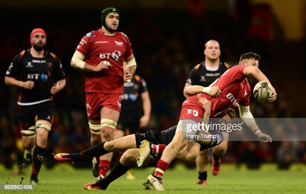 Steff Evans of Scarlets is tackled by Tom Prydie of Newport Gwent Dragons during the Guinness Pro12 match between Newport Gwent Dragons and Scarlets...