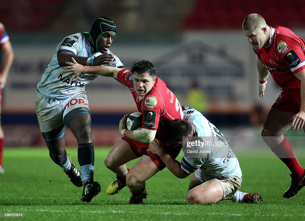 Steffan Evans of Scarlets is tackled by Camille Chat and Eddy Ben Arous of Racing 92 during the European Rugby Champions Cup match between Scarlets and Racing 92 at the Parc y Scarlets on November 21, 2015 in Llanelli, Wales.