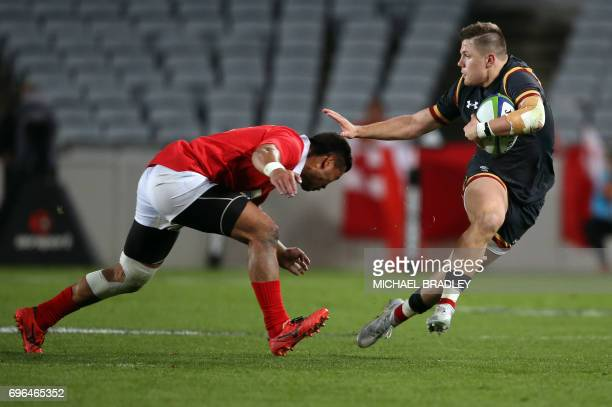Steffan Evans of Wales looks to fend off Siale Piutau of Tonga during the Tonga and Wales international rugby Test match played at Eden Park in...