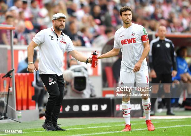 Steffen Baumgart, Head Coach of 1. FC Koeln passes Jonas Hector of 1. FC Koeln a water bottle during the Bundesliga match between 1. FC Köln and VfL...