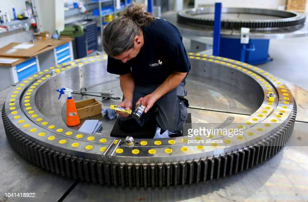 Steffen Haack works on a slewing bearing at company Hanse Drehverbindungen in Wismar Germany 30 September 2013 The firm signed a cooperation...