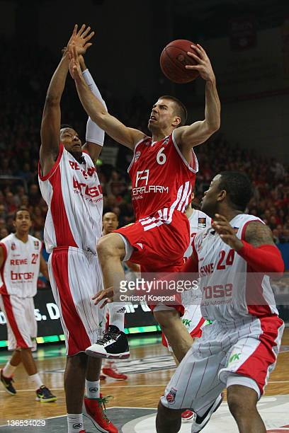 Steffen Hamann of FC Bayern Muenchen scores against Marcus Slaughter of Brose Baskets Bamberg and PJ Tucker of Brose Baskets Bamberg during the Beko...