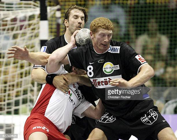 Steffen Stiebler and Karol Bielecki of Magdeburg against Dimitri Torgowanow of Essen during the first Final of the EHF Cup between SC Magdeburg and...
