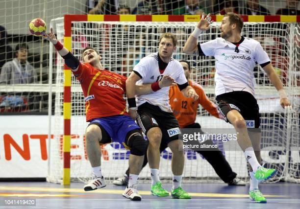 Steffen Weinhold and Oliver Roggisch of Germany block Aitor Arino Bengoechea of Spain during the men's Handball World Championships quarterfinal...