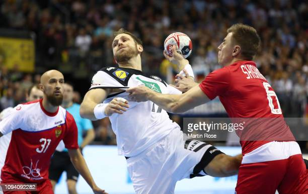 Steffen Weinhold of Germany is challenged by Danill Shishkarev of Russia during the 26th IHF Men's World Championship group A match between Russia...