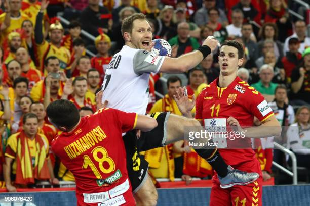 Steffen Weinhold of Germany is challenged by Filip Kuzmanovski of Macedonia during the Men's Handball European Championship Group C match between...