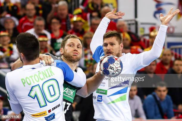 Steffen Weinhold of Germany is challenged by Gregor Potocnik of Slovenia during the Men's Handball European Championship Group C match between...