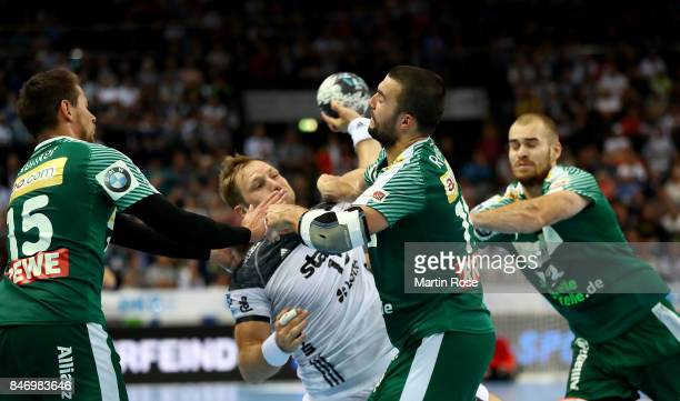 Steffen Weinhold of Kiel challenges Bastian Roscheck and Maximilian Janke of Leipzig for the ball during the DKB HBL Bundesliga match between THW...