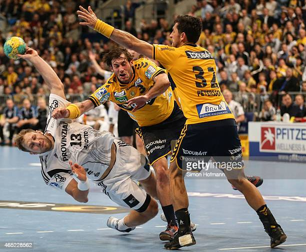 Steffen Weinhold of Kiel tries to score against Uwe Gensheimer and Alexander Petersson of RheinNeckar Loewen during the DHB cup quarter final match...