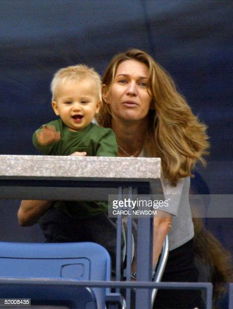 Steffi Graf holds her son Jaden Gil as they watch husband and father Andre Agassi's match against Justin Gimelstob 29 August 2002 at the US Open in...