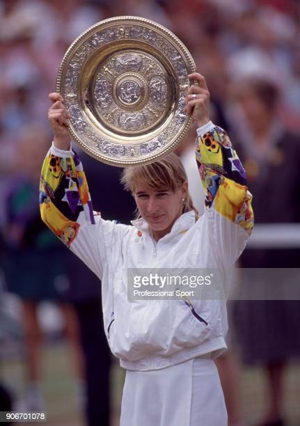 Steffi Graf of Germany lifts the trophy after defeating Jana Novotna of the Czech Republic in the Women's Singles Final of the Wimbledon Lawn Tennis...