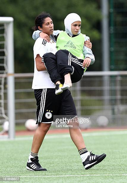 Steffi Jones director of German Football Association carries a participant during a training session at the NFV football school training ground on...