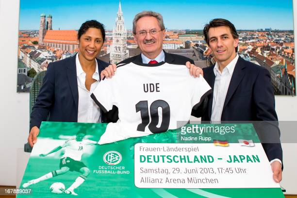 Steffi Jones hands over a ticket for a women's international match to Munich's mayor Christian Ude together with Juergen Igelspacher general manager...
