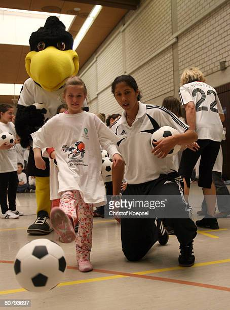 Steffi Jones President of the Organising Committee of the German Football Association for the 2011 FIFA Women's World Cup in Germany watches a child...